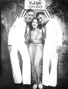 Earl 'Jitterbug' Pearson and Herman Toscano celebrate the end of the war by having their photograph taken with a Hotel Street hostess.