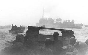 World War I vintage 'four stacker' destroyer USS Pruitt (DM 22) leads landing craft to fog-shrouded invasion beaches of Attu on 11 May 1943.  (US Navy photograph)